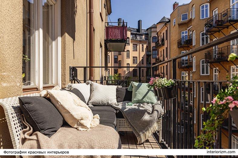 угловой диванчик с подушками на балконе