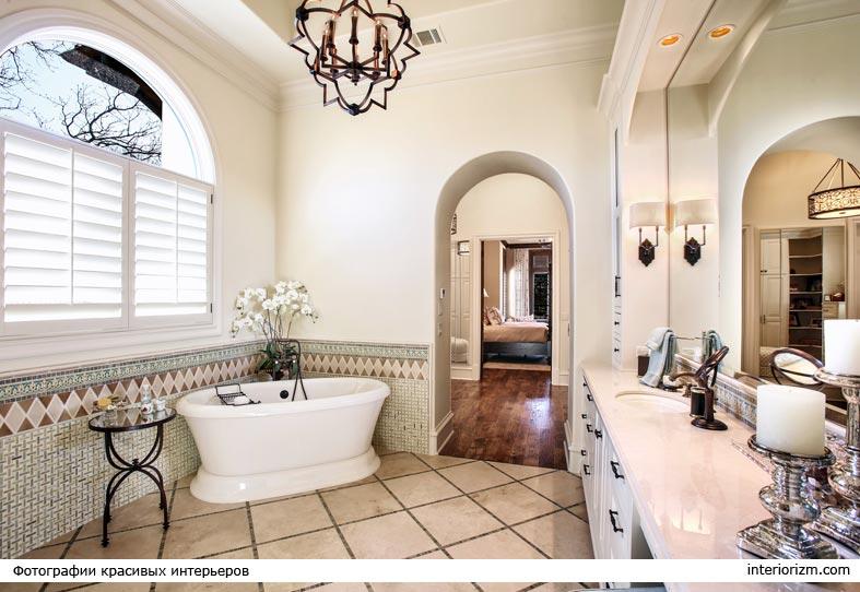 красивая ванная комната с большим зеркалом и люстрой